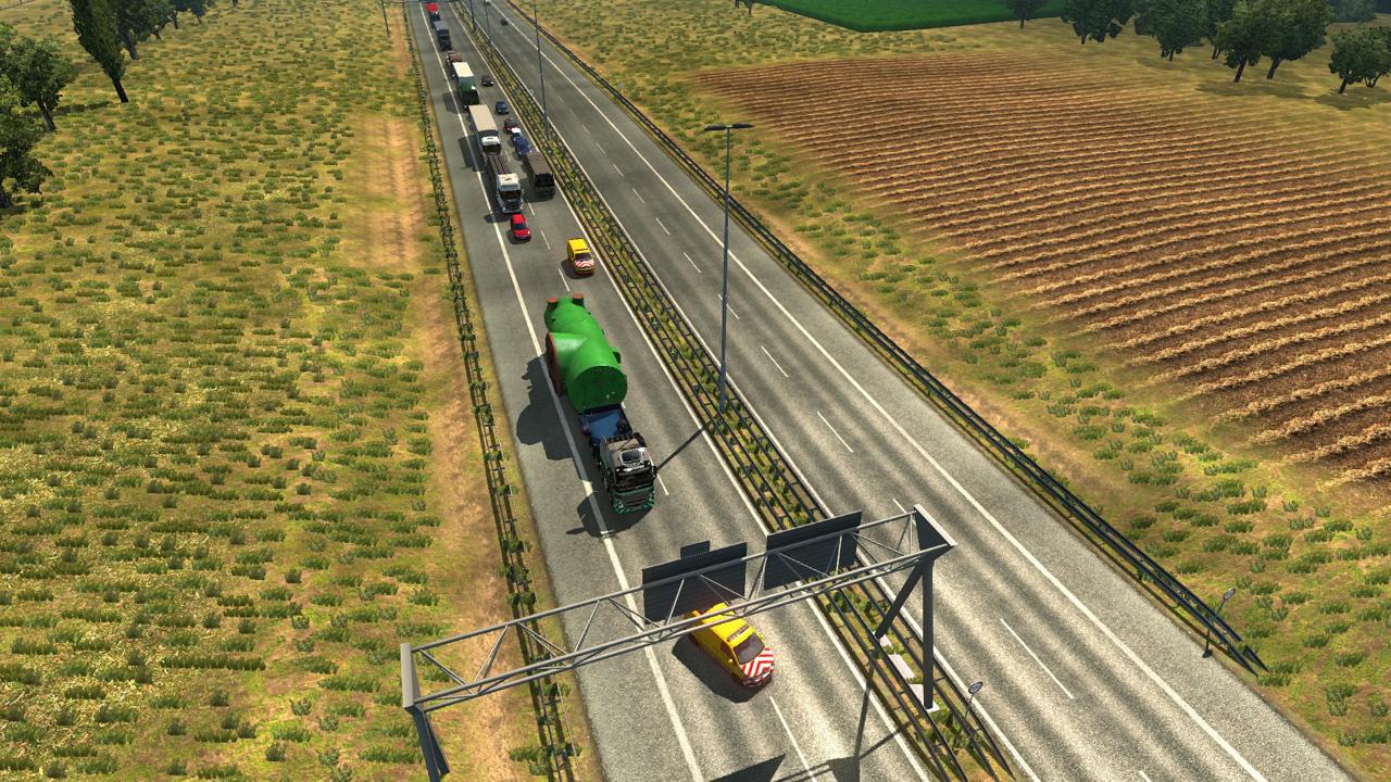 Schwerlast-LKW wechselt die Spur zwischen zwei Begleitfahrzeugen, dahinter Stau