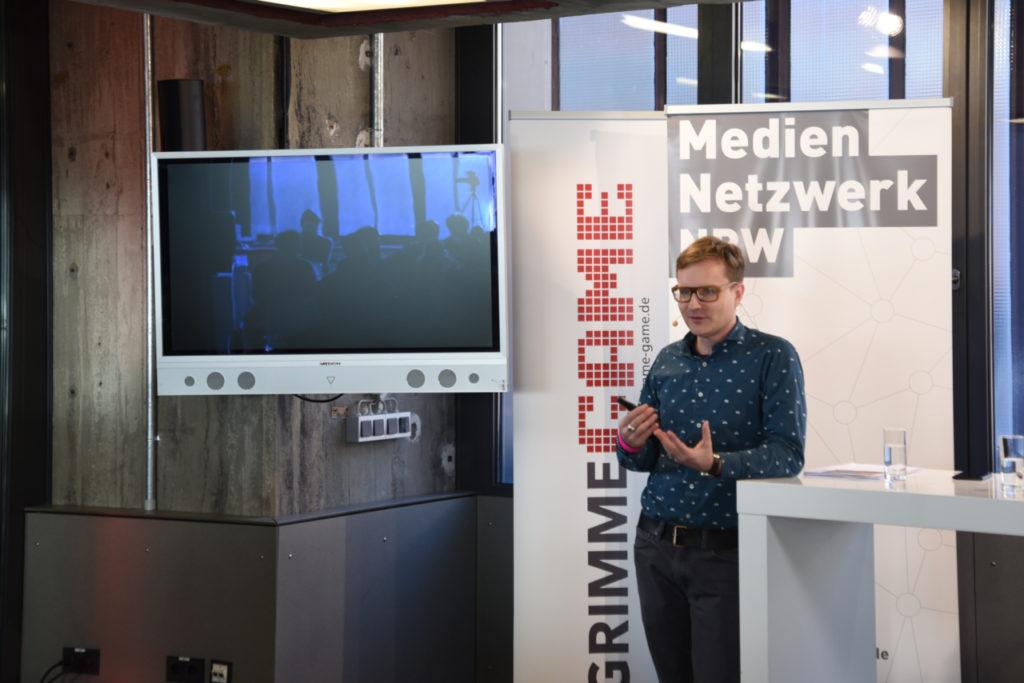 Andreas Garbe steht neben einem Tisch und hält einen Vortrag