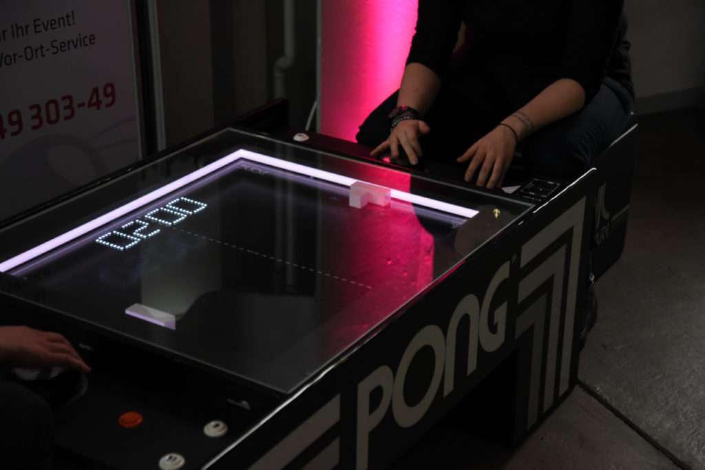 Zwei Personen spielen gegeneinander Pong auf einer Tisch-Version des Spiels