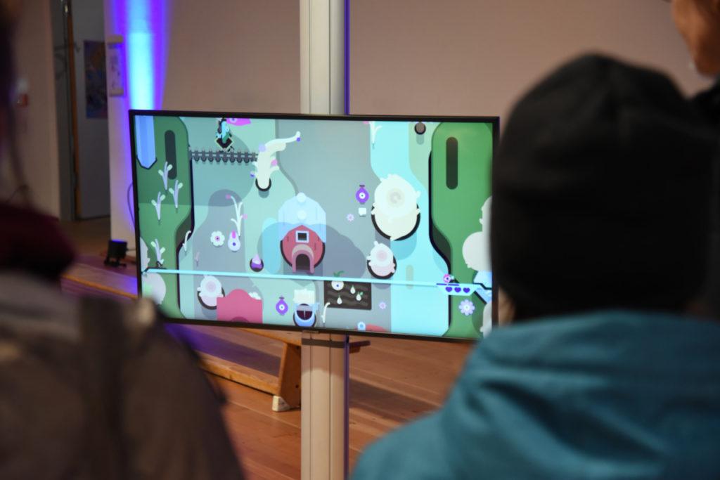 """Drei Personen schauen sich auf einem Bildschirm das Videospiel """"Tumbleseed"""" an"""